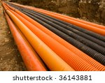 Orange and black plastic pipes in a ditch - stock photo