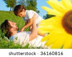 Happy childhood on green meadow, behind sunflower - stock photo