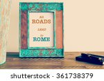 Small photo of Retro effect and toned image of a vintage photo frame next to fountain pen and notebook . Motivational quote written with typewriter font ALL ROADS LEAD TO ROME