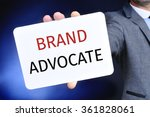 Small photo of closeup of a young caucasian businessman in a gray suit showing a signboard with the text brand advocate written in it
