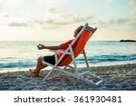 Man Relaxing On Beach At Sunset