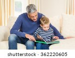 Father And Son Reading Book On...