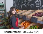 Attractive Turkish woman fills a wooden box with fresh mandarin oranges in the grocery
