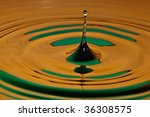 drop bouncing off a water surface - stock photo