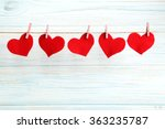 Small photo of Love hearts hanging on rope on a blue wooden background