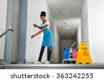 African Woman Mopping Corridor...