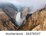 Morning fog lifts above the Lower Falls of the Yellowstone River - stock photo