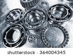 Small photo of ball-bearings, pinions against brushed aluminum, titanium and steel aerospace parts