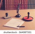 Small photo of Notary public tools. Themis with scales of justice and notarial acts in the background.