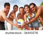 Group of people with a volleyball at the beach - stock photo
