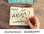 Small photo of Retro effect and toned image of a woman hand writing a note with a fountain pen on a notebook. Handwritten text ABM ALWAYS BE MARKETING, business success concept