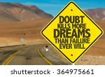 Small photo of Doubt Kills More Dreams Than Failure Ever Will sign on desert road