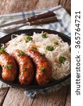 Small photo of Traditional fried sausage and sauerkraut on a plate close-up on the table. vertical