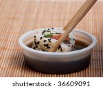 Dip sushi roll in the soy sauce - stock photo