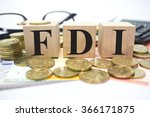 Small photo of Finance Concept with Stack of Coins, FDI or Foreign Direct Investment written