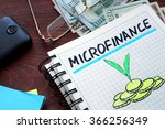 Small photo of Microfinance written on a notebook. Business concept.