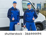 Portrait of happy technicians showing thumbsup while standing against truck - stock photo