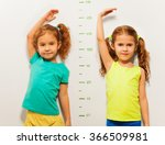 Two Girls Show Height On Wall...