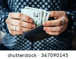 Small photo of Hands holding georgian lari bills and small money pouch