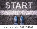 Small photo of Word Start written on an asphalt road with legs and shoes