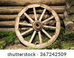 Old Wooden Coach Wheel Near Barn