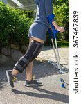 Small photo of Young woman wearing an adjustable leg brace to support and immobilize her knee post operative, side view, walking outdoors on crutches in a garden