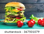 Big cheeseburger deluxe high on green wooden background in rustic style for gluttons