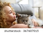 Stock photo young woman and cat on sofa in the room 367607015