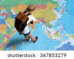 Small photo of Women traveler Is planning a tour her standing on the world map.She points to the map