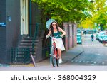 young happy woman on bike in... | Shutterstock . vector #368004329