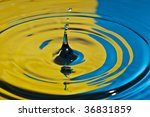 closeup of a water splash in yellow and blue tones - stock photo