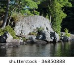 Cliffs with pine trees on a dark river - stock photo