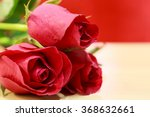 Three Red Rose On Wood Table.