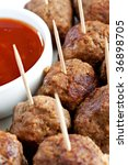 A platter of tasty meatballs, with a savory dipping sauce.  Perfect party food or appetiser.  Selective focus. - stock photo