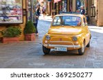 Small photo of San Marino, Italy - August 22, 2015: Old small car Fiat 500 moves down the street of San Marino