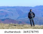 Small photo of Young tourist man standing on mountain. Happy young tourist man with backpack standing on rocky cliff and enjoying panoramic view over afforested mountains.