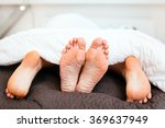 Stock photo couple having sex under blanket with their feet visible 369637949