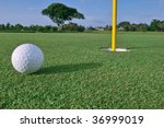 golf ball near hole and pin on florida golf course green, recently fertilized - stock photo