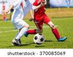 boys kicking football on the... | Shutterstock . vector #370085069