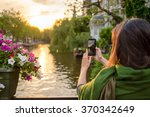Stock photo a tourist young women in amsterdam take pictures at a beautiful sunset on a bridge 370342649