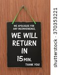 Small photo of We Will Return in 15 Minutes We Apologize for any inconvenience Thank You Blackboard sign hanging on wood door
