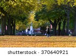 Small photo of TROWBRIDGE, UK - OCT 25, 2015: People walk through leafy tree lined public park. The UK is experiencing an 'Indian Summer' with above average temperatures and stunning autumnal colours.