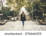 a woman walking down stairs in... | Shutterstock . vector #370666355