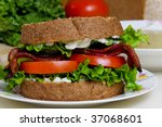 A BLT sandwich and a bowl of split pea soup with ingredients in the background - stock photo