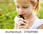 Small child holding a little black chick tenderly against her cheeks. - stock photo
