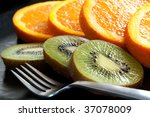 Slices of kiwi fruit and orange, on a black plate with fork.  Luscious healthy snacking. - stock photo