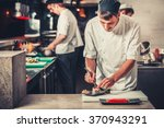 male cooks preparing sushi in... | Shutterstock . vector #370943291