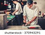 Male Cooks Preparing Sushi In...