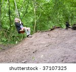 Young Boy Swinging On A Rope...