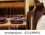 Mannequin in classical black jacket, suit shop in the background - stock photo